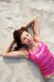 Mujer joven que asolea en la playa Fotografía de archivo libre de regalías