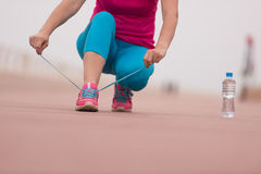 Mujer joven que ata cordones en las zapatillas de deporte Fotos de archivo