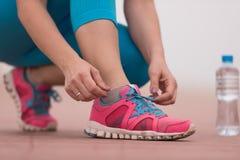 Mujer joven que ata cordones en las zapatillas de deporte Imágenes de archivo libres de regalías