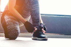 Mujer joven que ata sus cordones antes de ejercicio en gimnasio foto de archivo