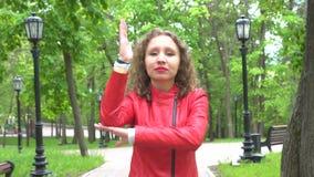 Mujer joven que aumenta la mano mientras que mira la cámara sobre fondo verde del parque almacen de metraje de vídeo