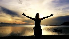 Mujer joven que aumenta la mano para arriba en la playa durante puesta del sol que sorprende Cámara lenta 1920x1080 metrajes