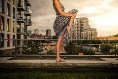 Mujer joven que aumenta su pierna en el top del tejado Foto de archivo