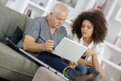 Mujer joven que ayuda al hombre mayor con el ordenador portátil Foto de archivo libre de regalías