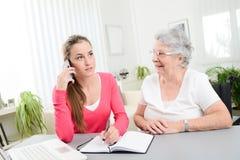 Mujer joven que ayuda a una vieja mujer mayor que hace papeleo y procedimientos administrativos con el ordenador portátil en casa Imagenes de archivo