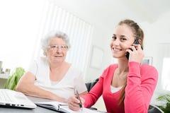 Mujer joven que ayuda a una vieja mujer mayor que hace papeleo y procedimientos administrativos con el ordenador portátil en casa Fotos de archivo