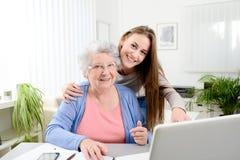 Mujer joven que ayuda a una vieja mujer mayor que hace papeleo y procedimientos administrativos con el ordenador portátil en casa Fotos de archivo libres de regalías