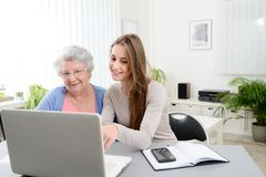 Mujer joven que ayuda a una vieja mujer mayor que hace papeleo y procedimientos administrativos con el ordenador portátil en casa Foto de archivo