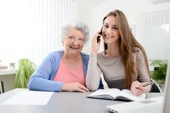 Mujer joven que ayuda a una vieja mujer mayor que hace papeleo y procedimientos administrativos con el ordenador portátil en casa Imagen de archivo libre de regalías