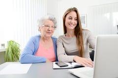 Mujer joven que ayuda a una vieja mujer mayor que hace papeleo y procedimientos administrativos con el ordenador portátil en casa Fotografía de archivo