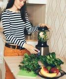 Mujer joven que azota verduras y las hojas en una licuadora foto de archivo