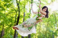Mujer joven que balancea en parque del verano fotos de archivo