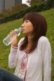 Mujer joven que bebe el agua mineral Foto de archivo libre de regalías