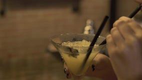 Mujer joven que bebe el cóctel alcohólico de la paja en el contador de la barra en restaurante Cierre encima de la consumición he almacen de metraje de vídeo