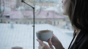 Mujer joven que bebe el café fragante Taza que se sostiene femenina Muchacha que se sienta en cafetería en la tabla de madera Ven almacen de metraje de vídeo
