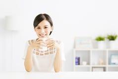 Mujer joven que bebe el café caliente del latte en sala de estar Fotos de archivo libres de regalías