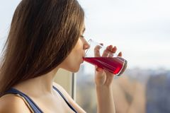 Mujer joven que bebe el jugo fresco natural de un vidrio, primer de la baya foto de archivo