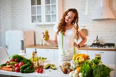Mujer joven que bebe el smoothie verde en la tabla de cocina con las frutas y verduras Concepto sano de la consumici?n Comida y d fotografía de archivo