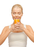 Mujer joven que bebe el zumo de naranja Foto de archivo libre de regalías