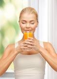 Mujer joven que bebe el zumo de naranja Fotos de archivo
