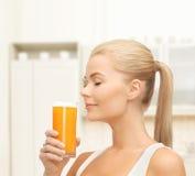 Mujer joven que bebe el zumo de naranja Fotos de archivo libres de regalías