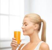Mujer joven que bebe el zumo de naranja Foto de archivo