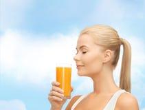 Mujer joven que bebe el zumo de naranja Imagen de archivo libre de regalías