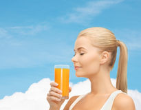 Mujer joven que bebe el zumo de naranja Fotografía de archivo libre de regalías