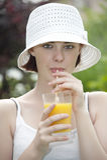 Mujer joven que bebe el zumo de naranja fresco Imagen de archivo libre de regalías