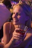 Mujer joven que bebe en un club nocturno Imagenes de archivo
