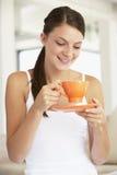 Mujer joven que bebe fuera de una taza anaranjada Fotos de archivo libres de regalías