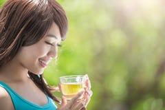 Mujer joven que bebe té caliente Fotos de archivo libres de regalías