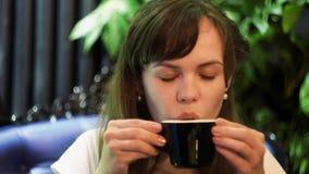 Mujer joven que bebe té caliente en el restaurante almacen de video