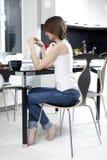 Mujer joven que bebe té negro Fotografía de archivo