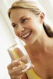 Mujer joven que bebe un vidrio de agua Fotografía de archivo