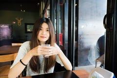 Mujer joven que bebe un vidrio de agua en café del arte Foto de archivo