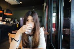 Mujer joven que bebe un vidrio de agua en café del arte Imágenes de archivo libres de regalías