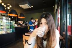Mujer joven que bebe un vidrio de agua en café del arte Imagen de archivo libre de regalías