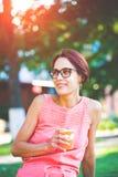 Mujer joven que bebe una bebida en el parque Imagen de archivo