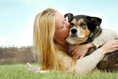 Mujer joven que besa al pastor alemán Dog Outside Foto de archivo