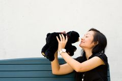 Mujer joven que besa el oso de peluche Imagenes de archivo