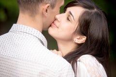 Mujer joven que besa a su novio Fotos de archivo