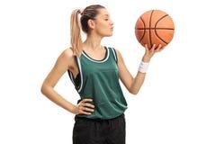 Mujer joven que besa un baloncesto Imagenes de archivo