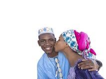 Mujer joven que besa a un hombre joven en la mejilla, aislada Fotografía de archivo libre de regalías