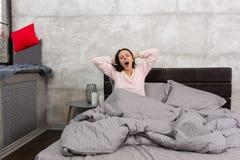 Mujer joven que bosteza y que estira mientras que se sienta en la cama y Imagen de archivo libre de regalías