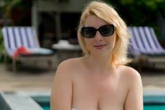 Mujer joven que broncea cerca de piscina Imagen de archivo