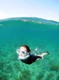 Mujer joven que bucea bajo el agua Foto de archivo