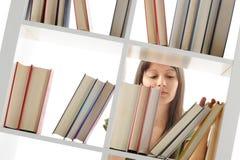 Mujer joven que busca un libro en la biblioteca Imagen de archivo