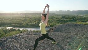 Mujer joven que calienta antes de entrenamiento de la aptitud en la salida del sol por la mañana Muchacha que estira al aire libr metrajes