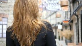 Mujer joven que camina abajo de la calle metrajes